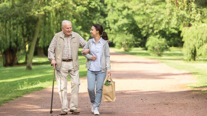 Female caregiver helping senior man with shopping