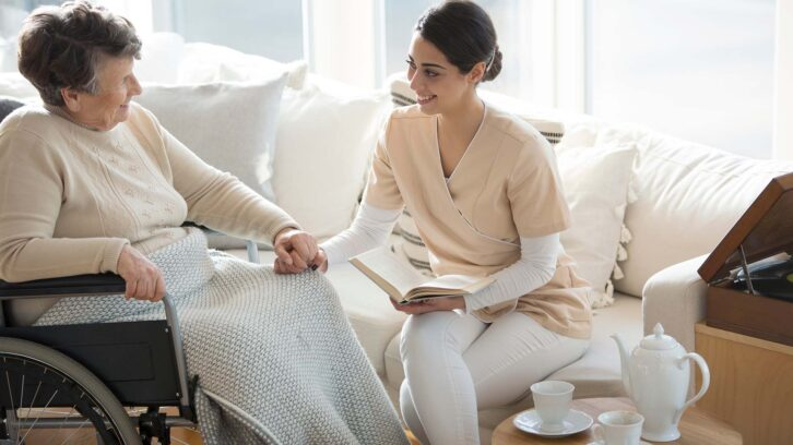 Caregiver reading with woman in wheelchair