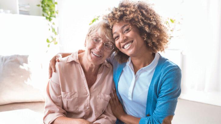 Cheerful home caregiver embracing senior woman
