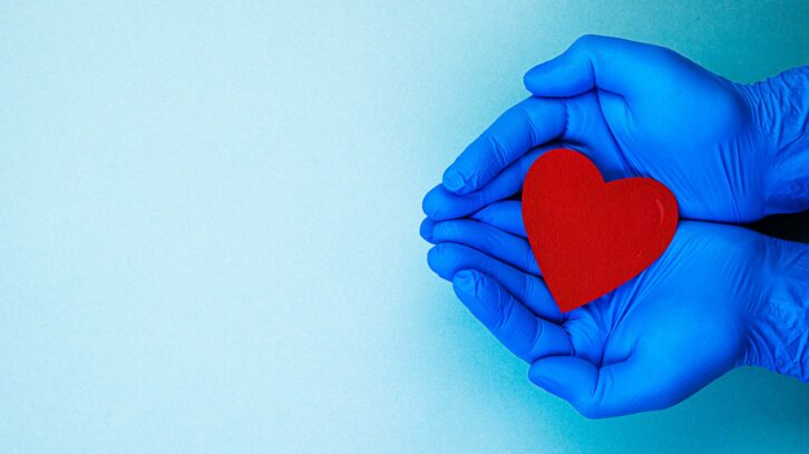 Hands wearing gloves holding paper heart