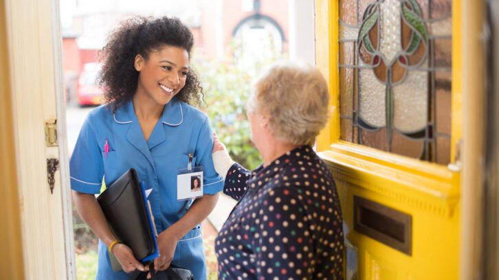Home care nurse greeting older woman at door