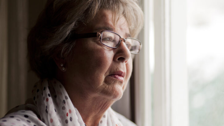 Lonely senior woman looking out window